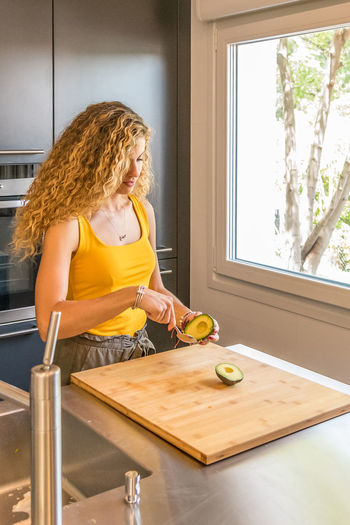 Woman with curly hair cutting avocado on cutting board in kitchen