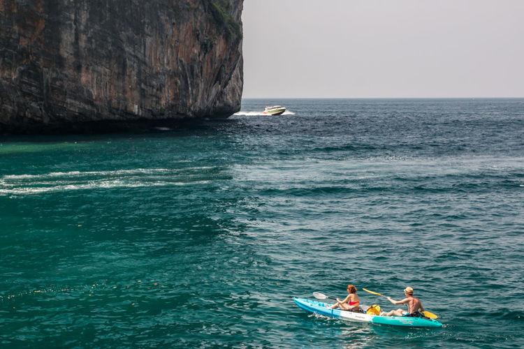 People kayaking on sea against sky