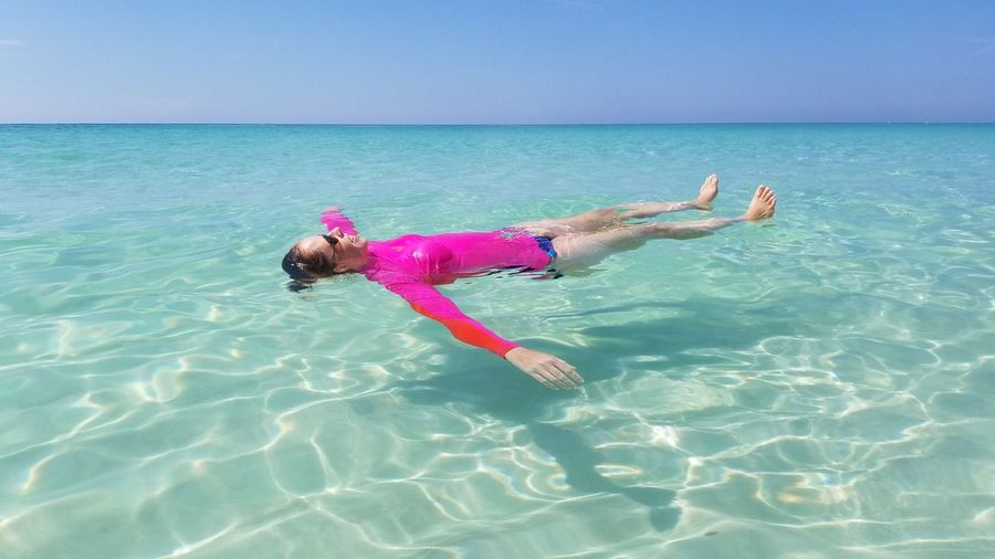 Full Length Of Woman Swimming In Sea Against Clear Sky