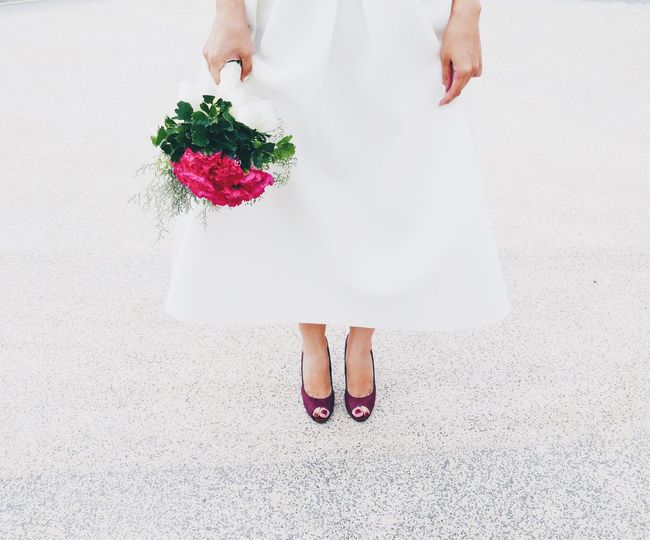 Low Section Of Bride Holding Rose Bouquet While Standing On Textured Floor