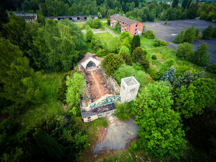 High angle view of abandoned house amidst trees on field