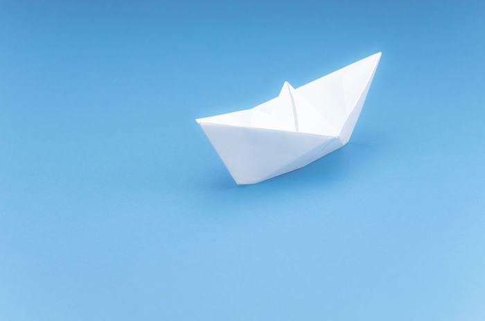 paper sailing boat - blue sea Art And Craft Blue Blue Background Close-up Colored Background Copy Space Craft Creativity Cut Out Folded High Angle View Indoors  Lightweight Minimalism No People Origami Paper Paper Boat Simplicity Single Object Still Life Studio Shot Summer White Color