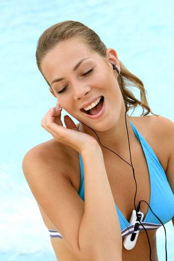 young blond woman listening to music with MP3 players at the pool Beautiful Happy Holiday Listening Music Music Summer Holidays Woman Beautiful Woman Bikini Blond Girl Happyness Leisure Leisure Activity Lifestyles Mp3 Player Outdoors Pretty Relaxation Smiling Swimming Pool Vacation Vacations Water Wellbeing