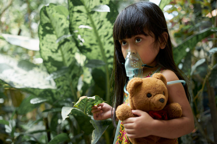 Girl breathing with nebulizer while standing with teddy bear by plants