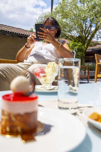 Woman Using Smart Phone and Strawberry Cake in a Restaurant. Ready To Eat Adult Cake Communication Drink Food Food And Drink Freshness Glass Holding Leisure Activity Lifestyles Luxury Mobile Phone One Person Outdoors Plate Refreshment Restaurant Selective Focus Strawberry Table Technology Wireless Technology Women
