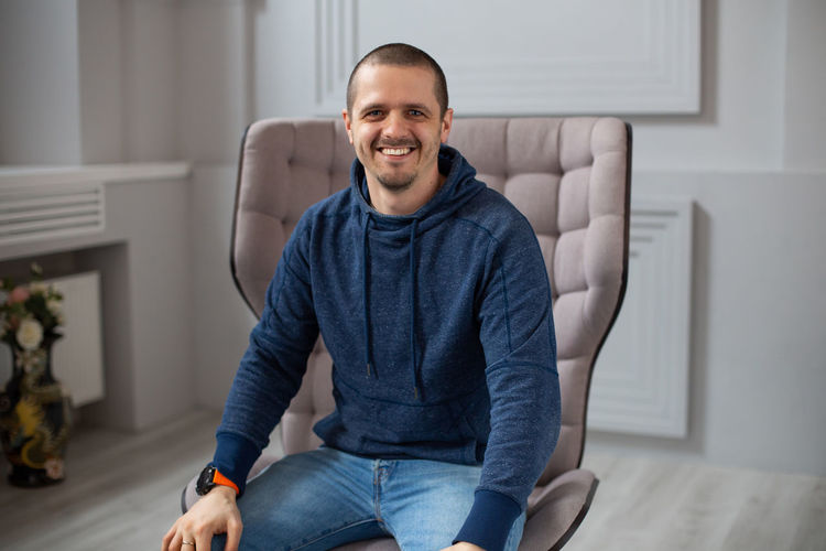 Man in dark blue hoodie smiling and looking in camera. Portrait of casual weared male. One Person Smiling Indoors  Three Quarter Length Looking At Camera Young Adult Portrait Happiness Sitting Front View Casual Clothing Lifestyles Home Interior Emotion Real People Furniture Young Men Sofa Jeans