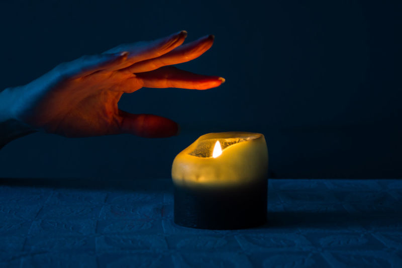 Close-up of hand touching burning candle