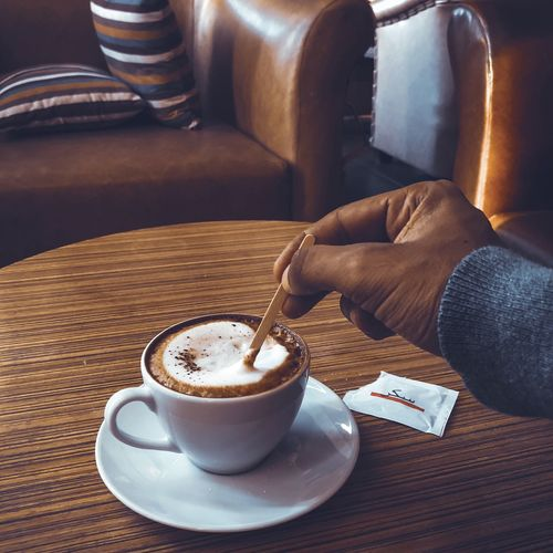 coffee Coffee Drink Coffee - Drink Food And Drink Refreshment Coffee Cup Mug Freshness Unrecognizable Person Frothy Drink Table Indoors  Cappuccino Hand Body Part Human Body Part Human Hand One Person Cup Real People