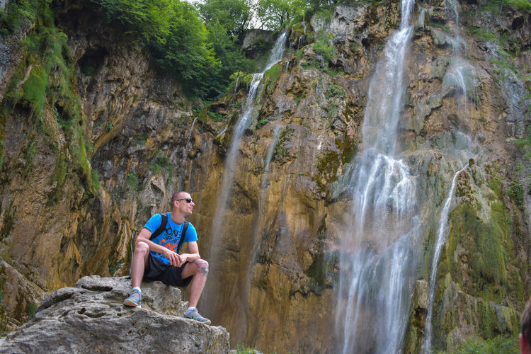 Low angle view of young man wearing sunglasses sitting on rock against waterfall