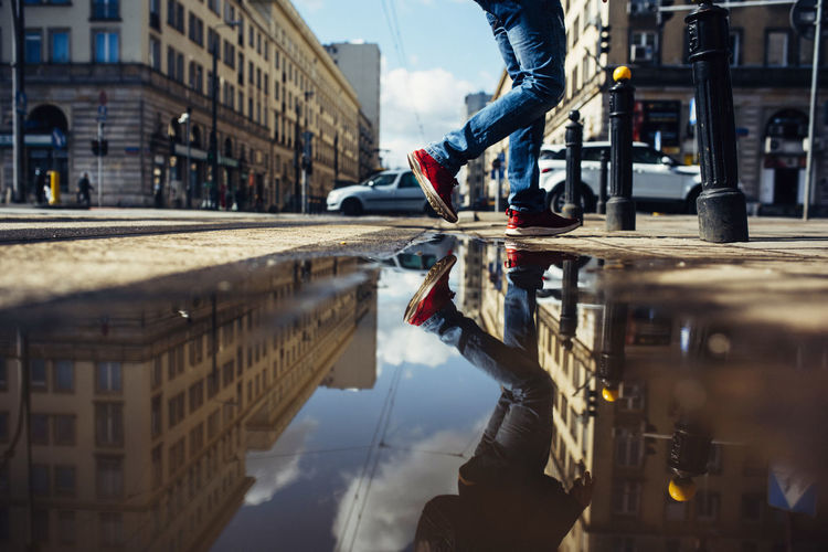 Reflection of man in puddle on street
