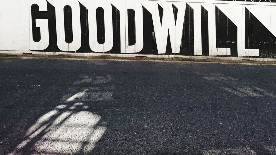 Text on road sign against wall in city