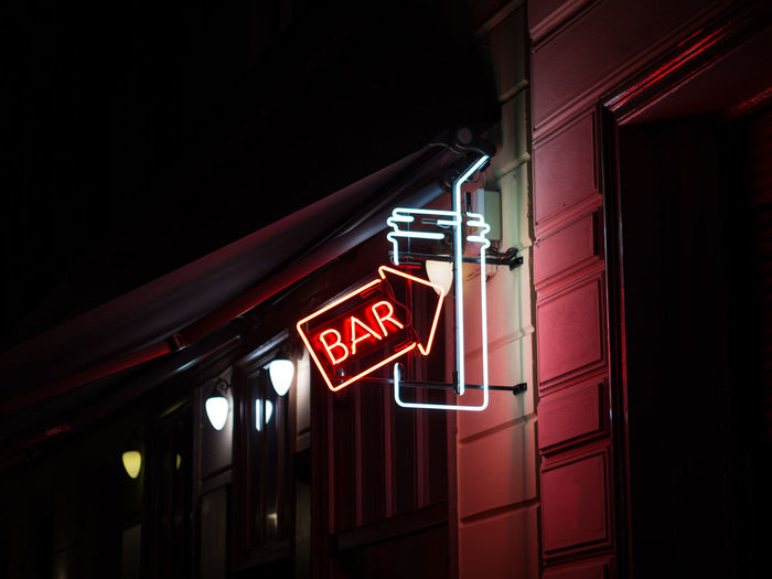 Low Angle View Of Illuminated Bar Sign At Night