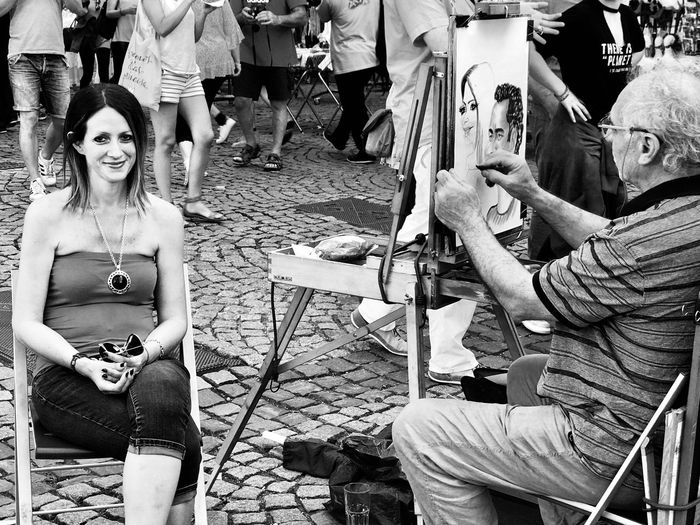 Artist painting woman sitting on chair at town square