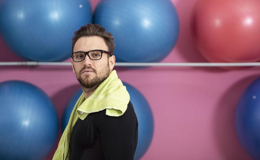 Portrait of man wearing eyeglasses standing against fitness balls