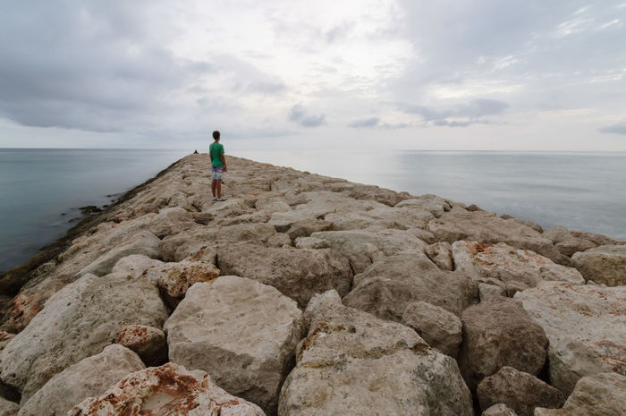 Young man on the seawall in the beach at sunrise in a cloudy summer day with copy space Beauty In Nature Bored Breakwater Cloud - Sky Contemplating Day Discovering Idyllic Leisure Activity Lifestyles Millennials Nature Outdoors Rock - Object Scenics Seawall Sky Summer Tranquil Scene Tranquility Vacations Water Young