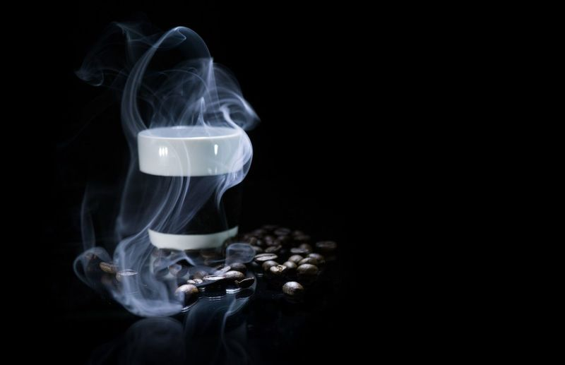 Roasted coffee bean with coffee cup against black background