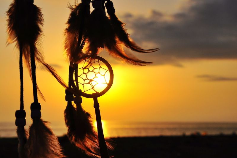 Close-Up Of Silhouette Dreamcatcher Against Sky During Sunset