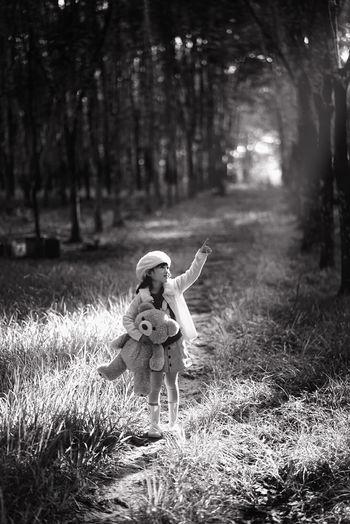 Full length of girl on field in forest