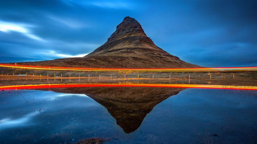 Kirkjufell mountains and reflection with car light, Iceland. Beauty In Nature Cloud - Sky Day Environment Idyllic Lake Landscape Mountain Mountain Peak Nature No People Reflection Scenics - Nature Sky Symmetry Tranquil Scene Tranquility Travel Destinations Water Waterfront