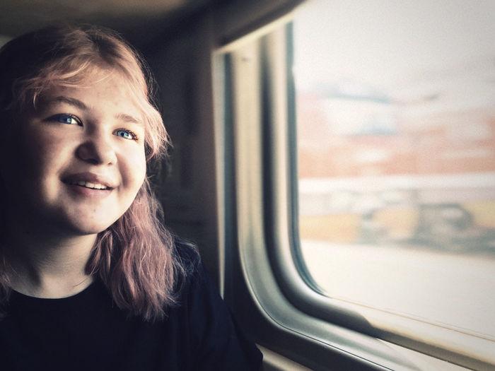 Smiling teenage girl sitting by window in train