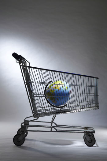 Globe In Shopping Cart Against White Wall