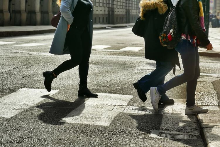 Low section of people walking on street in city