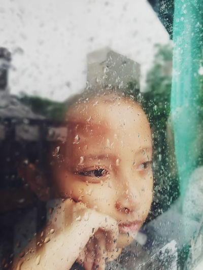 Close-up portrait of boy seen through wet glass window