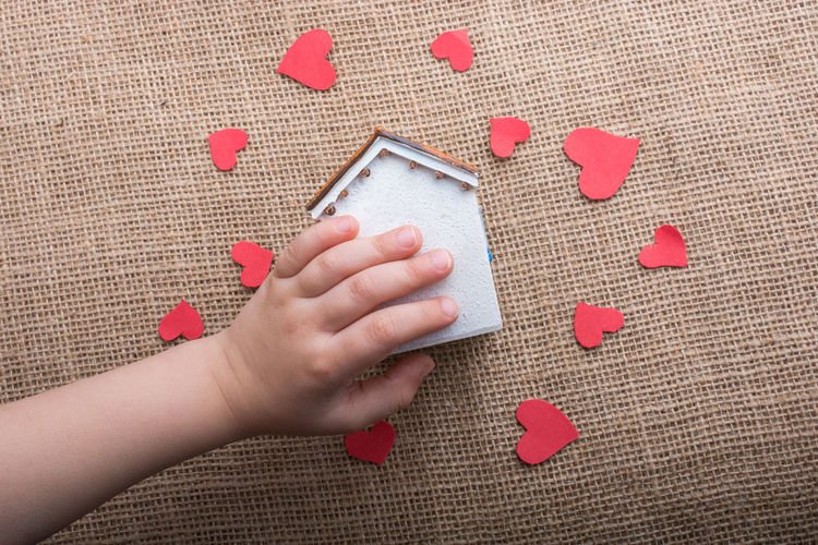 Cropped Hand Of Woman Holding Model Home With Red Heart Shapes On Table