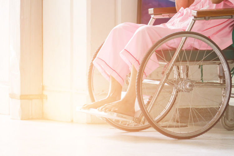 Low Section Of Senior Woman Sitting On Wheelchair At Hospital