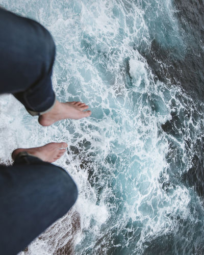 Low Section Of Person Sitting Over Flowing Water