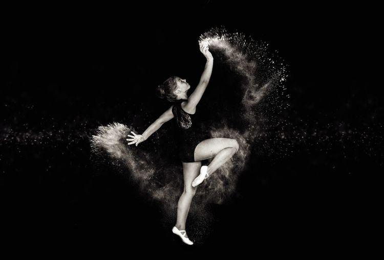 Full length of girl dancing against black background