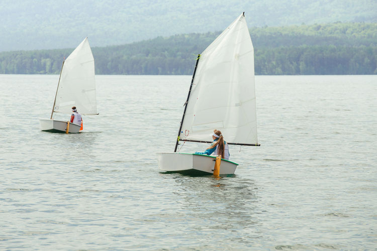 People sailing on sailboat in sea