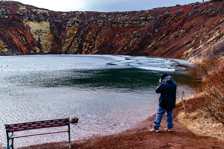 Rear View Of Man Standing By Frozen Crater Lake