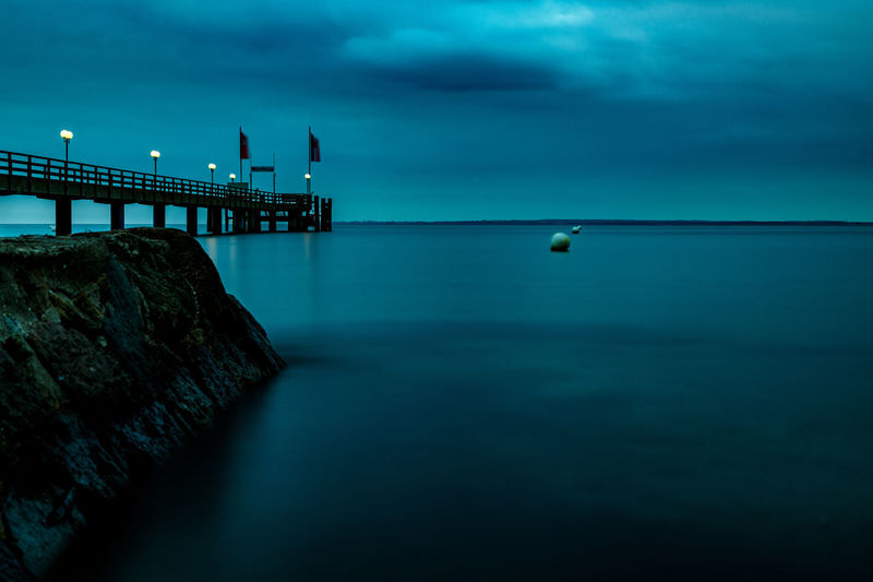 Long exposure of a pier with a breakwater in the foreground
