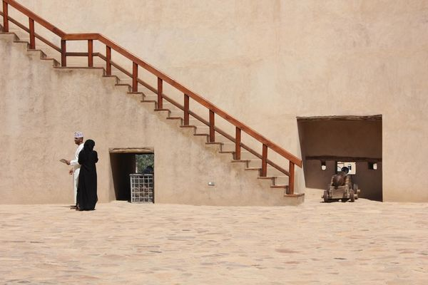 Nizwa Fort Castle in Oman Arabian Architecture Castle Nizwa Fort Oman Arab Arabic Architecture Day Fortress Nizwa Oman_photo Oman_photography Sandstone Two Persons The Graphic City