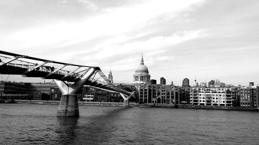 Millennium footbridge over thames river with st paul cathedral in city against sky
