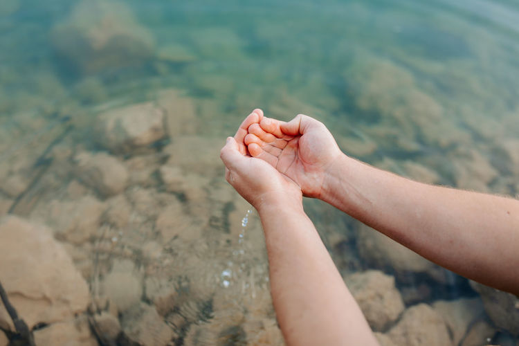 Cropped image of person hand against blurred water