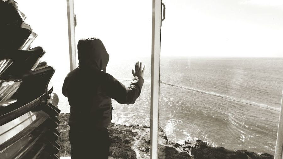 Rear View Of Hooded Boy Looking Through Glass Window At Observation Point
