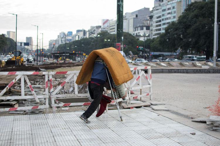 Disabled man carrying mattress on street