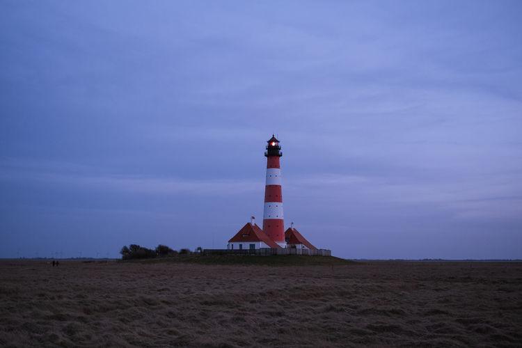 Lighthouse on beach by building against sky