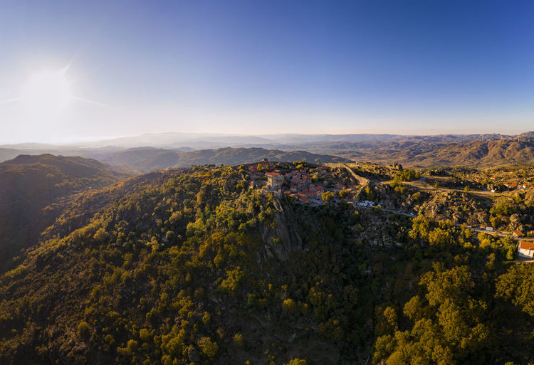 Drone aerial panorama of historic village of sortelha with castle and with turbines