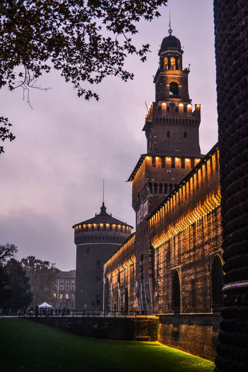 The Castle in Milan Right After The Dawn. Castle Evening Light Milan,Italy Nightphotography Architecture Belief Building Building Exterior Built Structure Castle Light Cloud - Sky Dusk History Illuminated Italy Nature No People Outdoors Sky Spire  The Past Tourism Travel Travel Destinations Tree