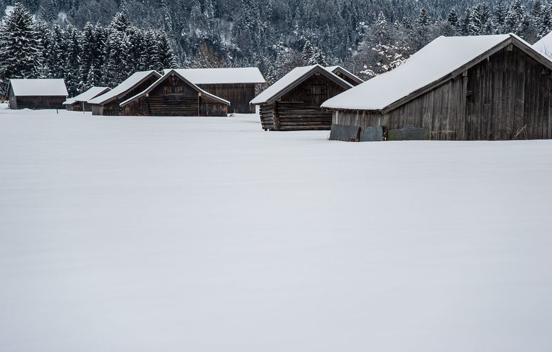 Houses on snow covered field against buildings