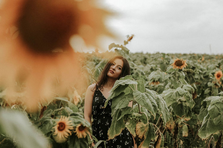 Young Woman Standing Amidst Sunflowers On Field Against Sky