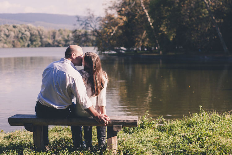 Rear view of couple sitting on riverbank