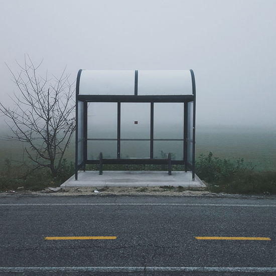 Empty bus stop at roadside by field during foggy weather