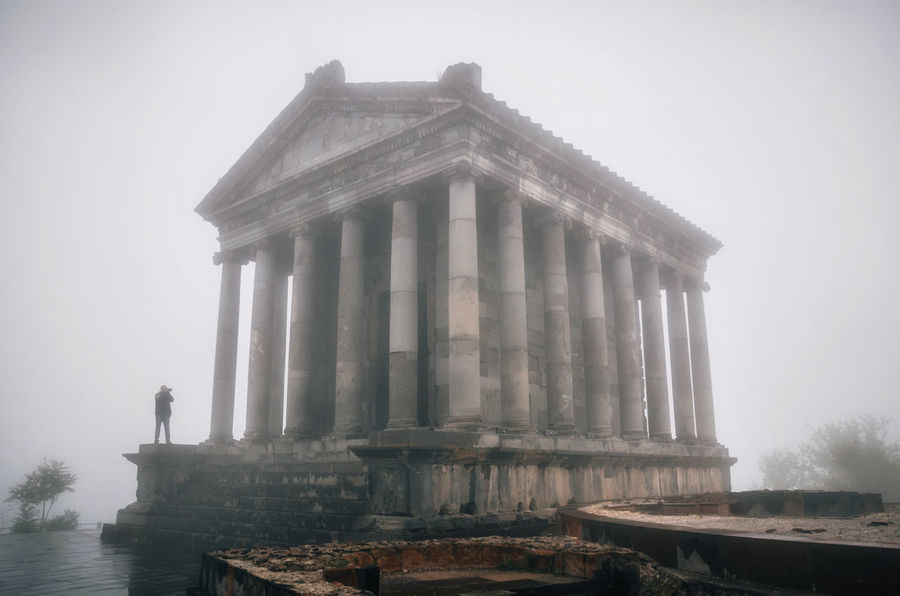 Garni hellenistic pagan Temple with silhouette of tourist taking photo in fog, Republic of Armenia Armenia Ancient Ancient Civilization Architectural Column Architecture Building Exterior Built Structure Fog History Outdoors Religion The Past Tourism Travel Travel Destinations