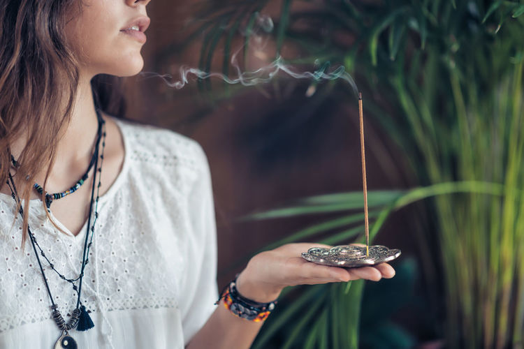 Young Woman Holding Burning Incense