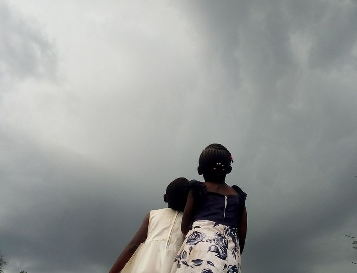 Low angle view of sisters looking at storm clouds