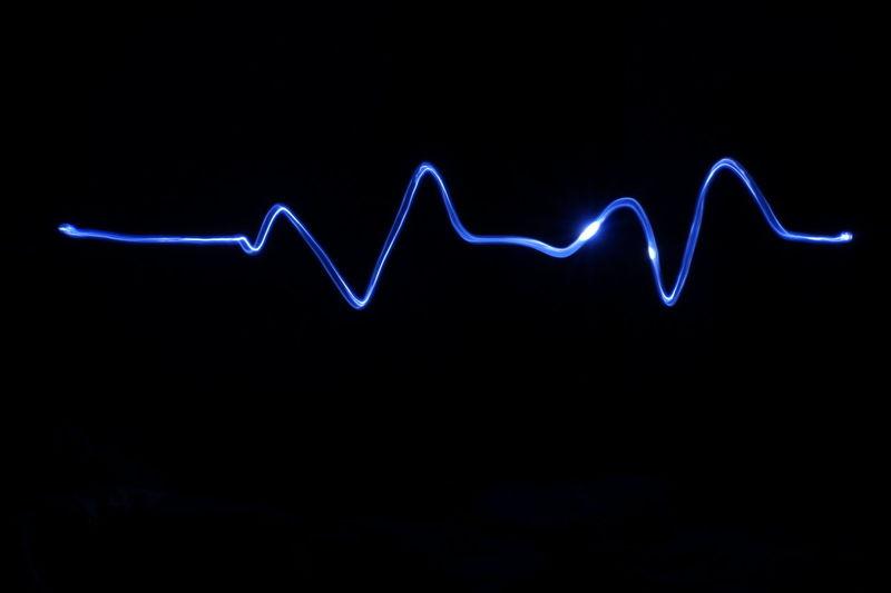 Illuminated pulse trace against black background